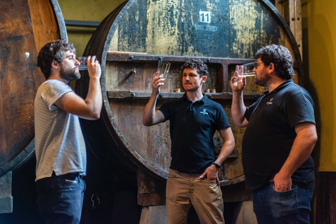 Gorka Arizkorreta, director of marketing, and brothers Joseba and Hur Astarbe, taste one of the 'kupelas' with cider of this season.
